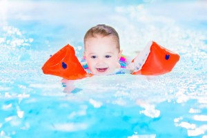 Happy laughing toddler girl having fun in a swimming pool
